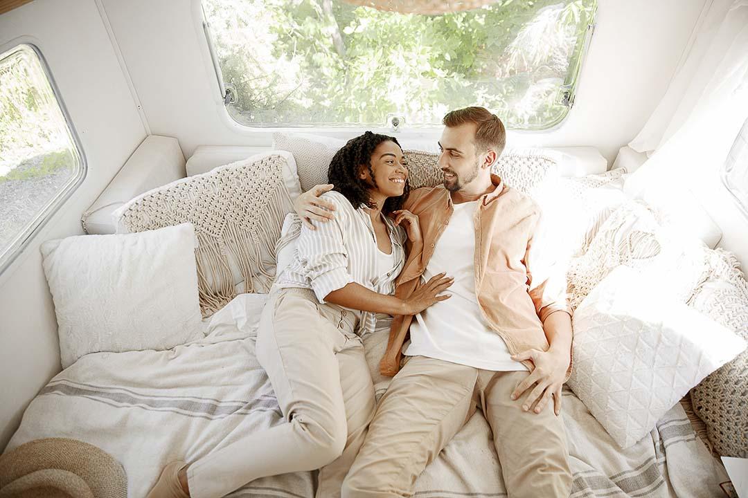 Un couple couché dans leur lit de roulotte