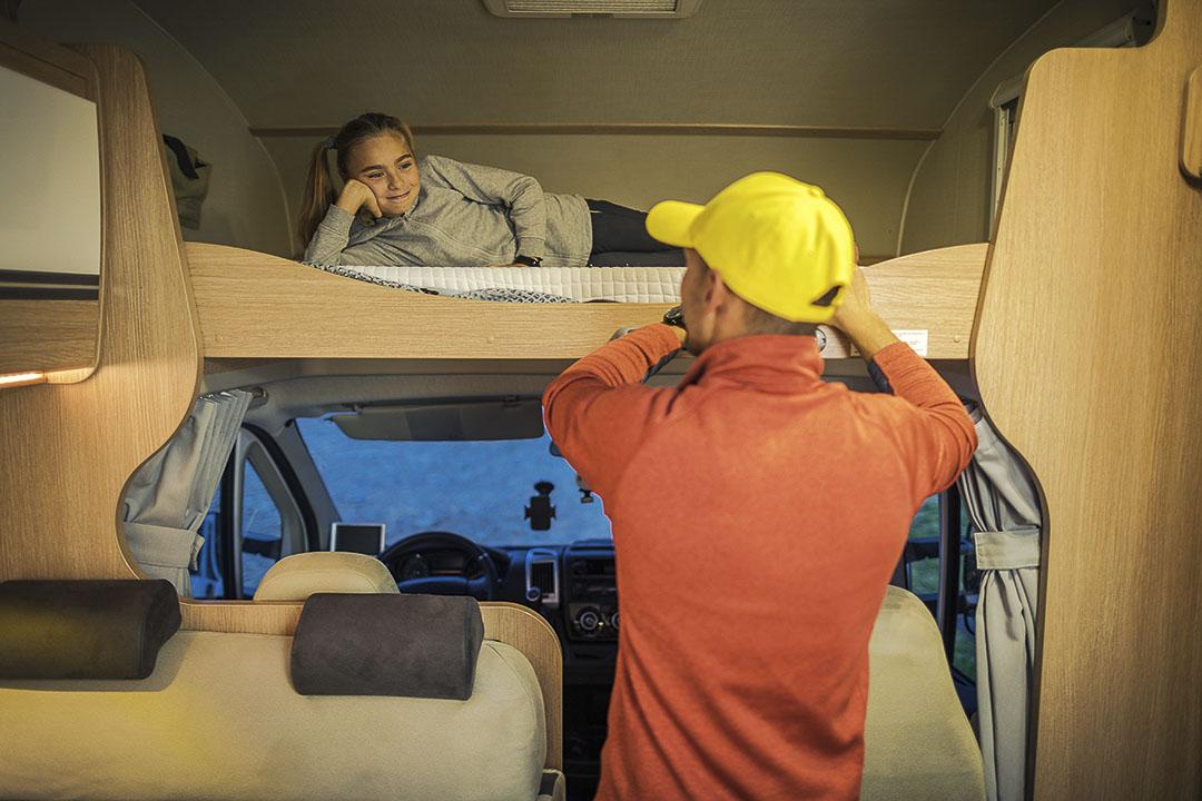 deux personnes dans une roulotte avec la femme dans le lit et l'homme debout