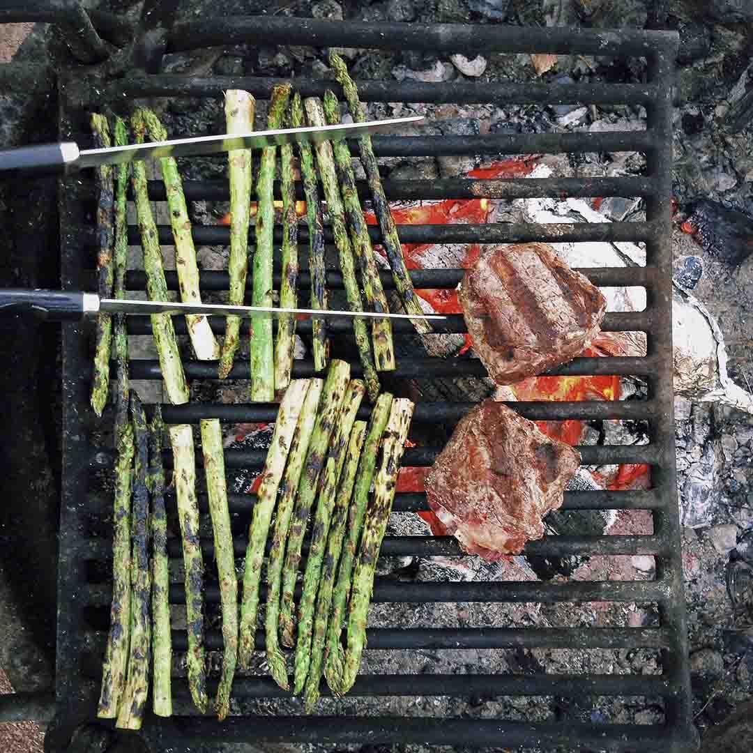 des asperges et deux morceaux de viande sur une grille avec un feu de camping en dessous