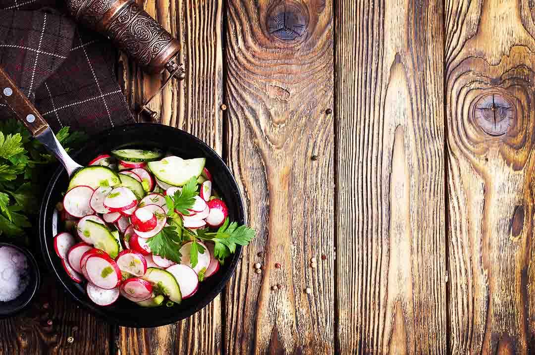 un bol de salade avec radis et concombre sur une table en bois