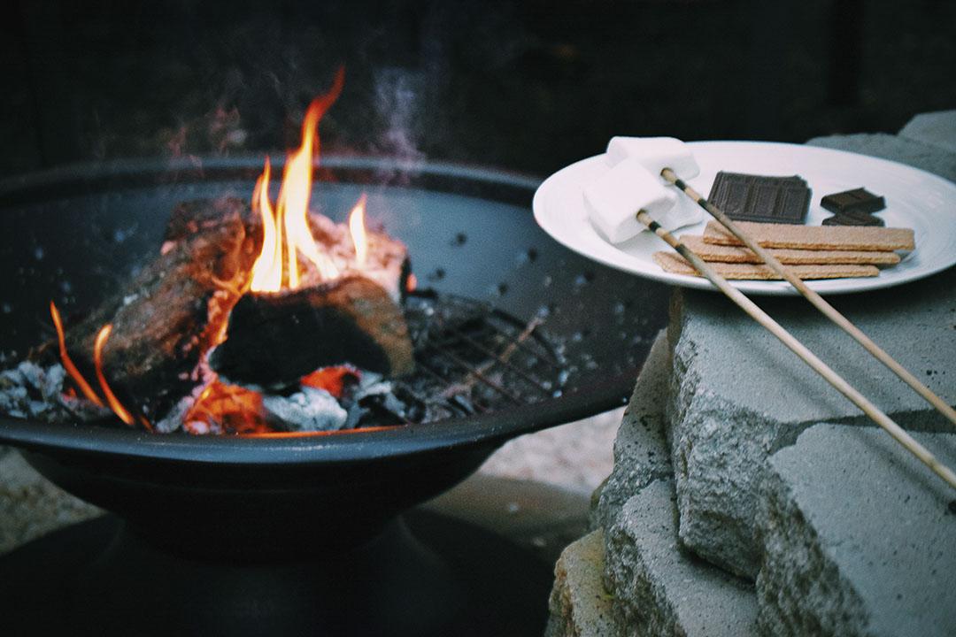 feu de camp avec le nécéssaire pour faire des S'mores: biscuits, chocolat et guimauves